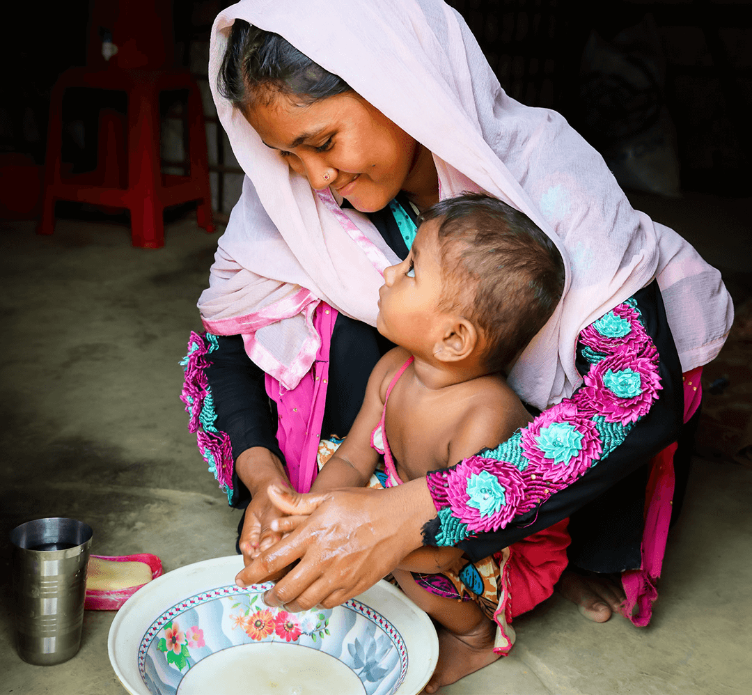 With Castle Water's support, we've worked to improve hygiene practices in Cox's Bazar, Bangladesh. Here Halima Khatum*, 19, washes her hands with her baby Laila*.
