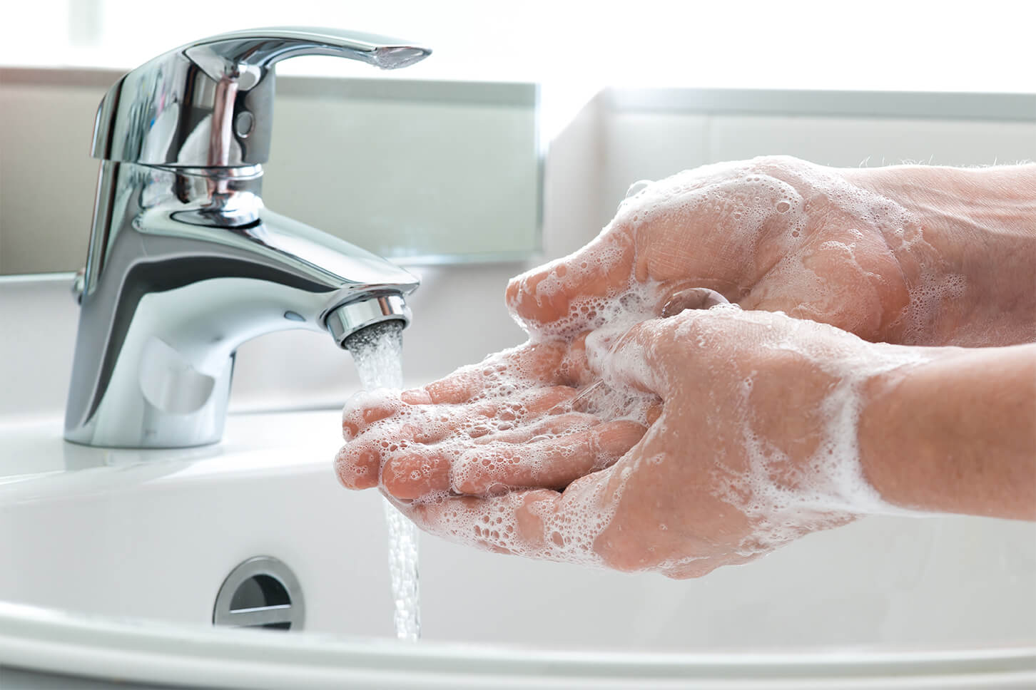 hands being washed with soap under a running tap