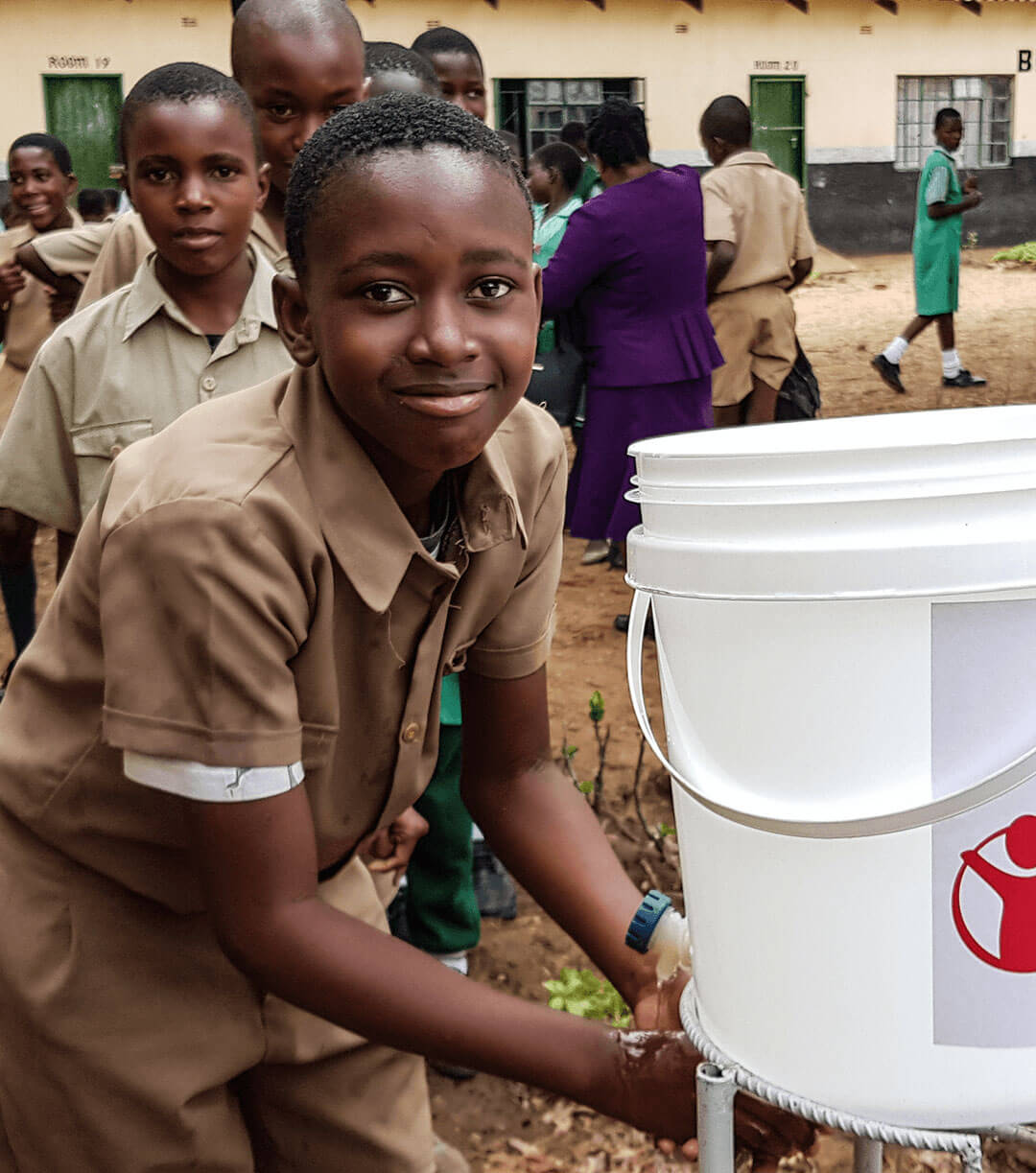 A student from a school in Gokwe North district, Zimbabwe, uses a handwashing station provided by Save the Children's Emergency Health Unit.