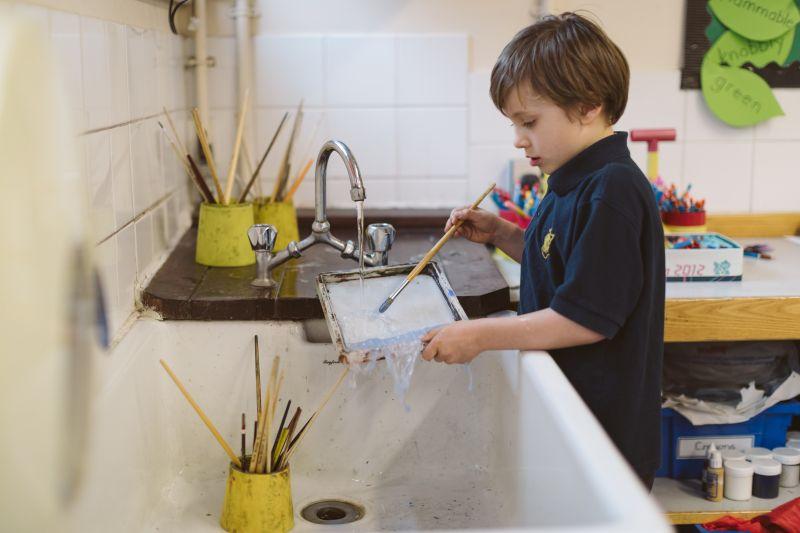 Boy washing paint tray